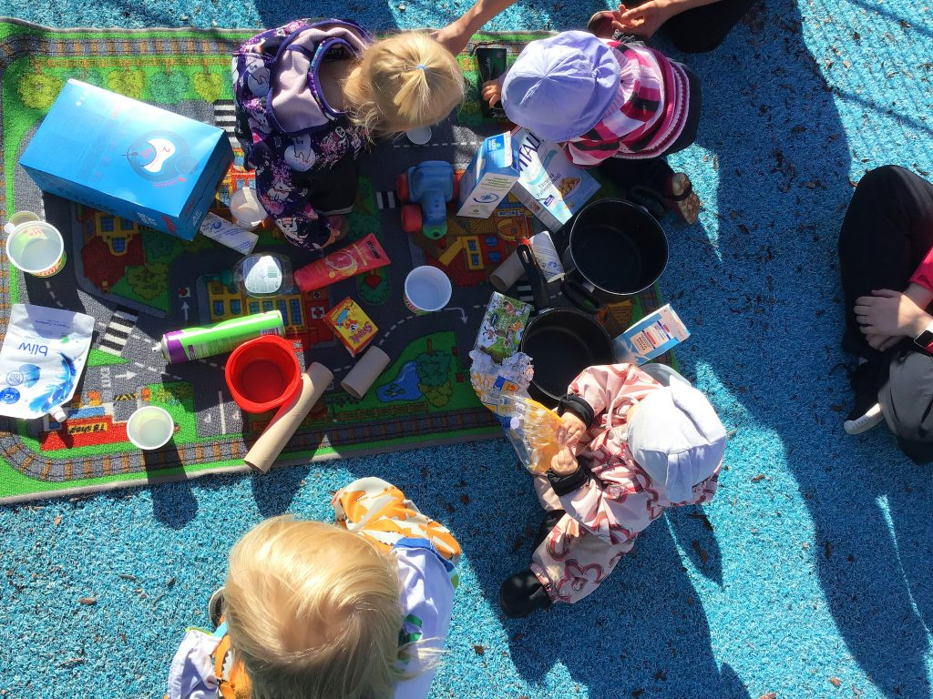 Lapset harjoittelevat kierrättämistä.