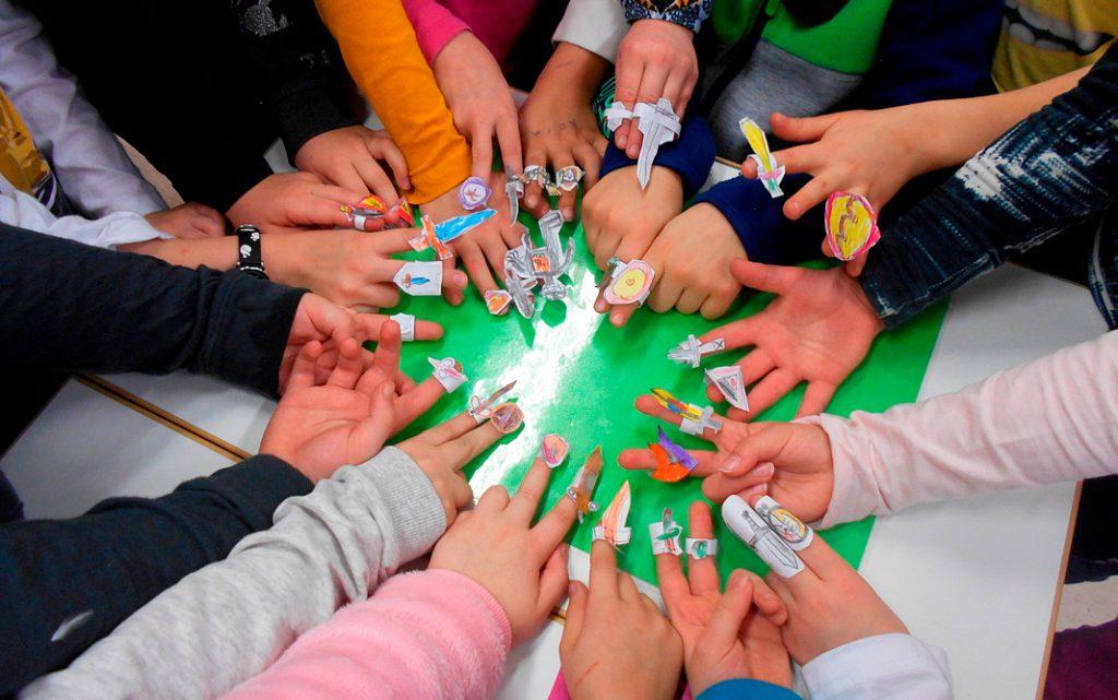 Vihreä lippu -kerhon jäsenet esittelevät tekemiään sormikuvioita.